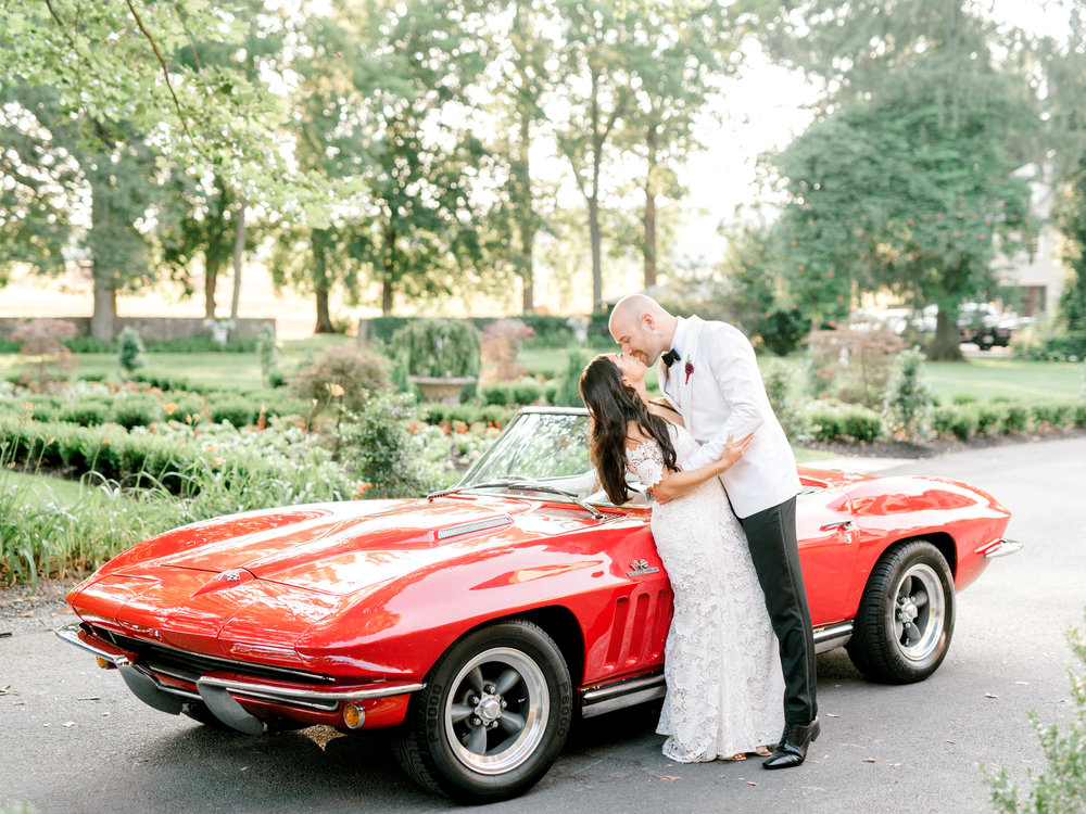 Colorful and modern summer wedding at Hotel du Village. Red sports car portrait.