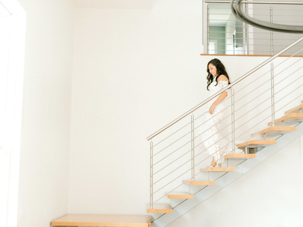 Lindsey descends the stairs of this light filled AirBnb as she heads to her bright and modern summer wedding at Hotel du Village.