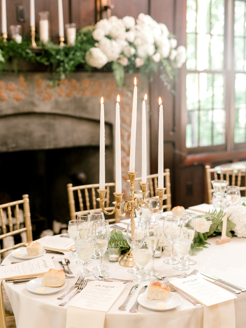 Tall white taper candles in a gold candlestick holder on add a touch of elegance and opulence to the tables of this bright and modern summer wedding at Hotel du Village.