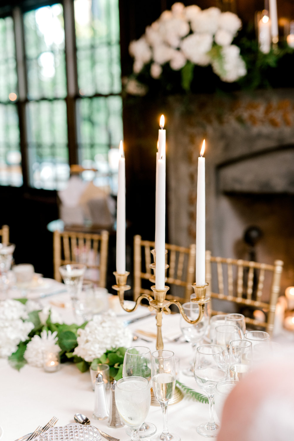 Gold candelabras with white taper candles add a touch of opulence and elegance to this bright and modern summer wedding at Hotel du Village.