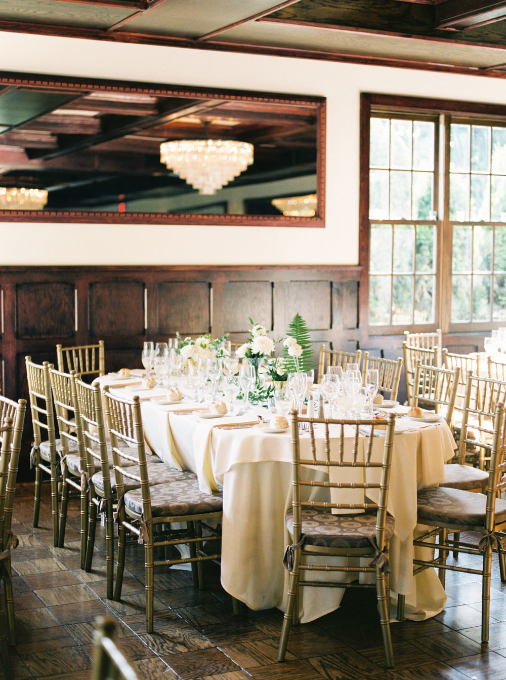 The contrast of dark wood and the bright walls and table linens and gold chairs give this historic space at Hotel du Village a modern feel that's perfect for a summer wedding.