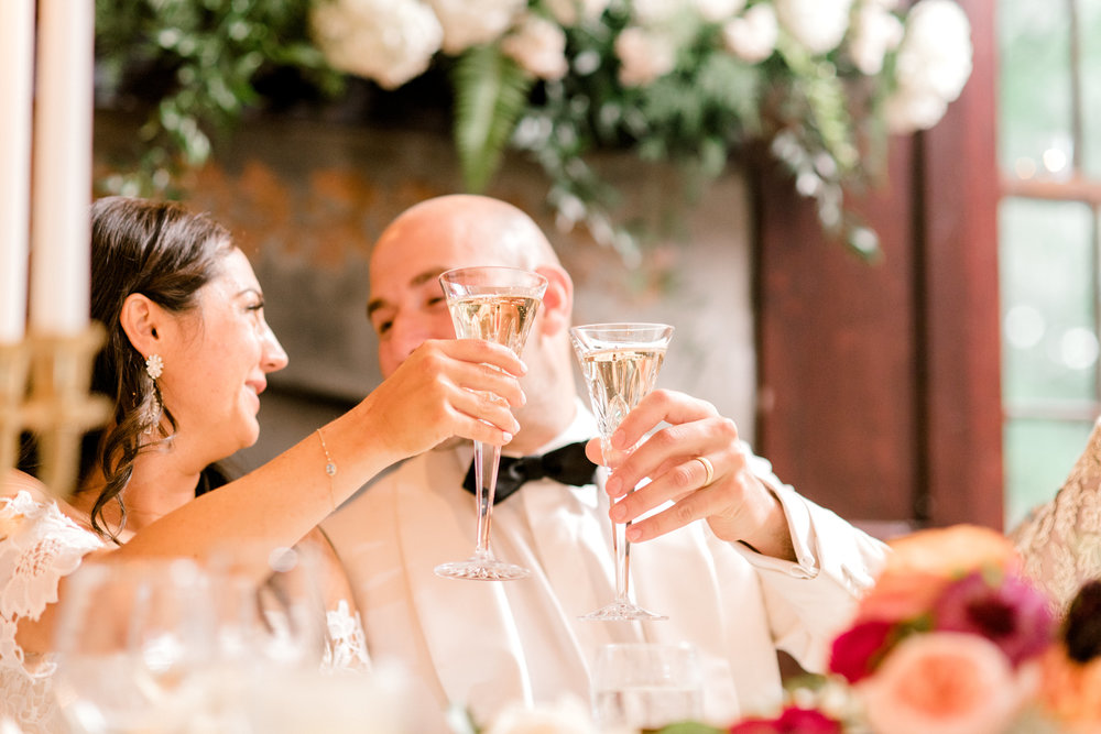 Cheers to the happy couple as they clink glasses at their modern elegant summer wedding at Hotel du Village.