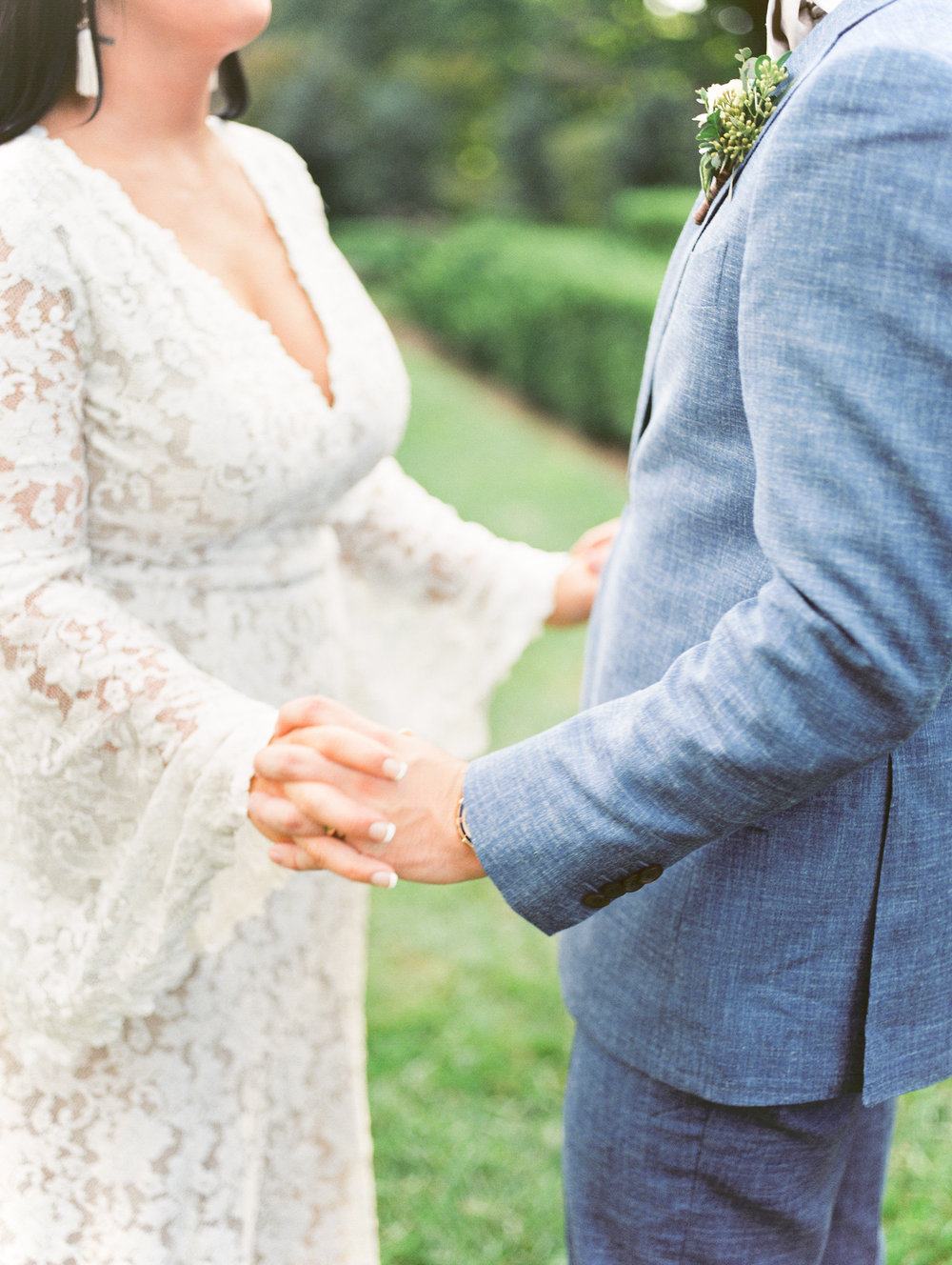 A sweet moment holding hands at this bright boho chic Tyler Gardens wedding in Bucks County, and we still can't get over this BHLDN gown or that light blue suit.