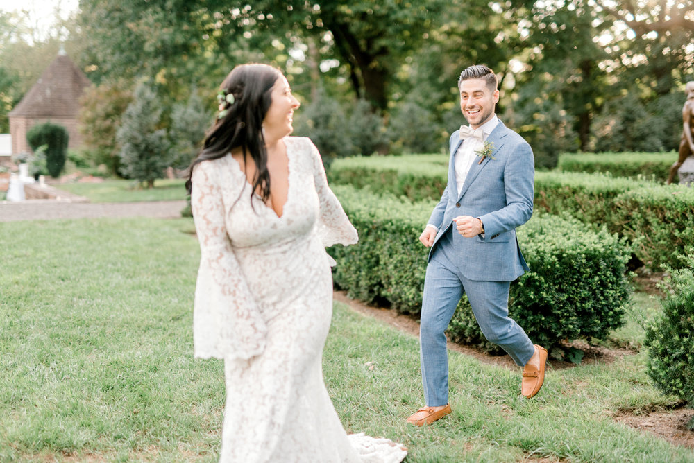 Chasing each other in style through the garden, we loved Alicia's bell sleeved lace dress paired with Mike's light blue suit for this bright boho chic Tyler Gardens wedding in Bucks County