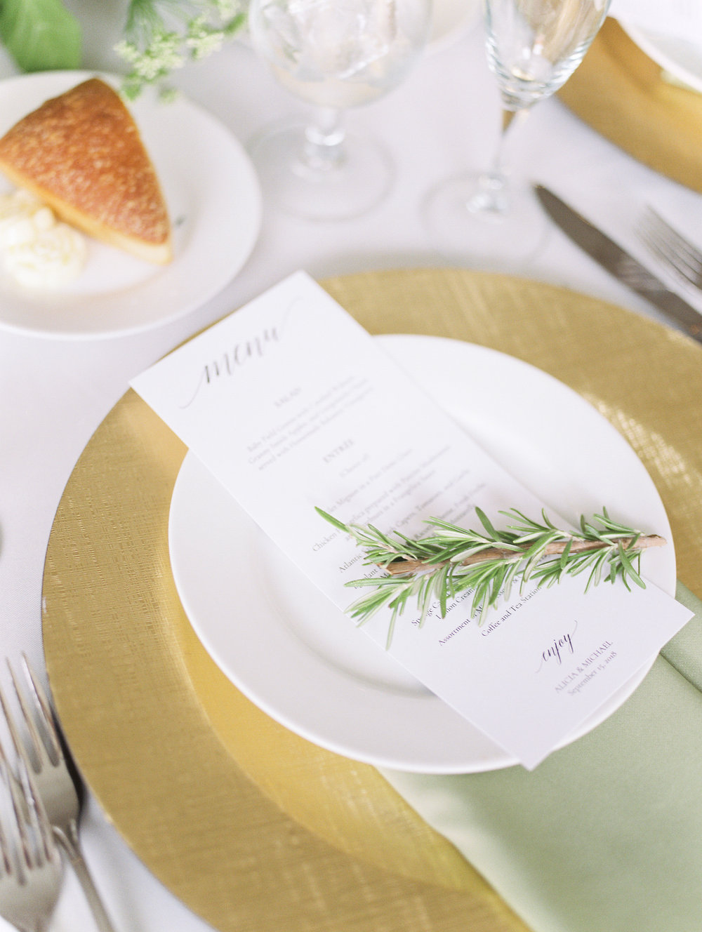 Beautiful and minimal menus topped with a sprig of Rosemary bring all the European vibes to this white and gold place setting at this bright boho chic Tyler Gardens wedding in Bucks County