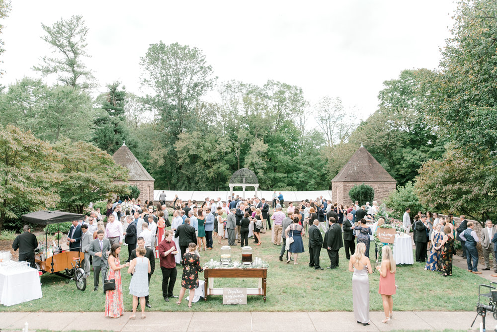 All gathered together in the garden, this cocktail hour brings right into an Italian style garden from this bright boho chic Tyler Gardens wedding in Bucks County