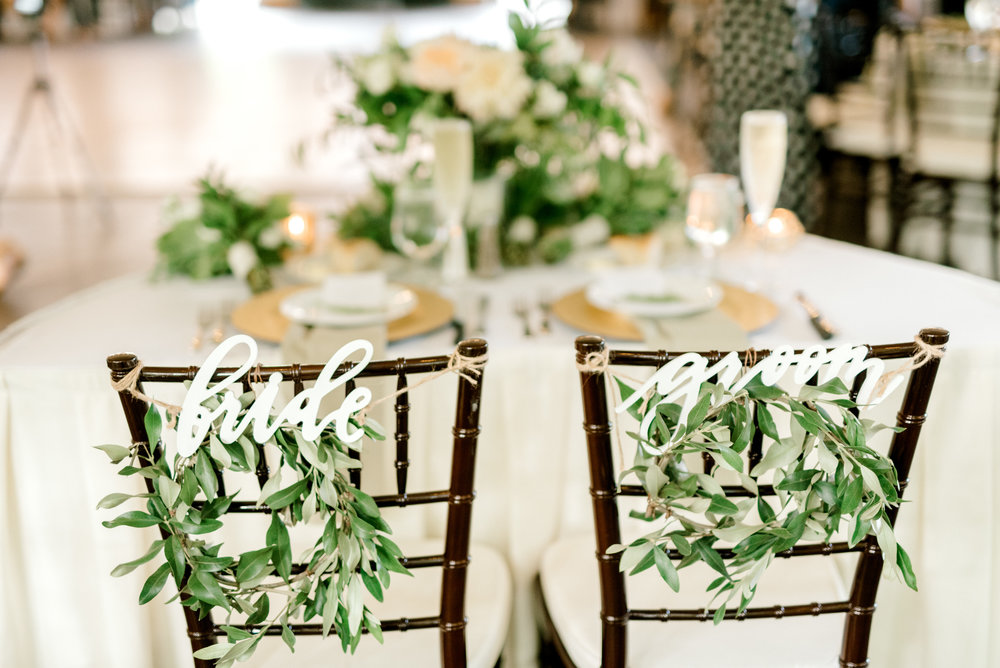 little green wreaths with laser cut signs identify the sweetheart table for this bright boho chic Tyler Gardens wedding in Bucks County