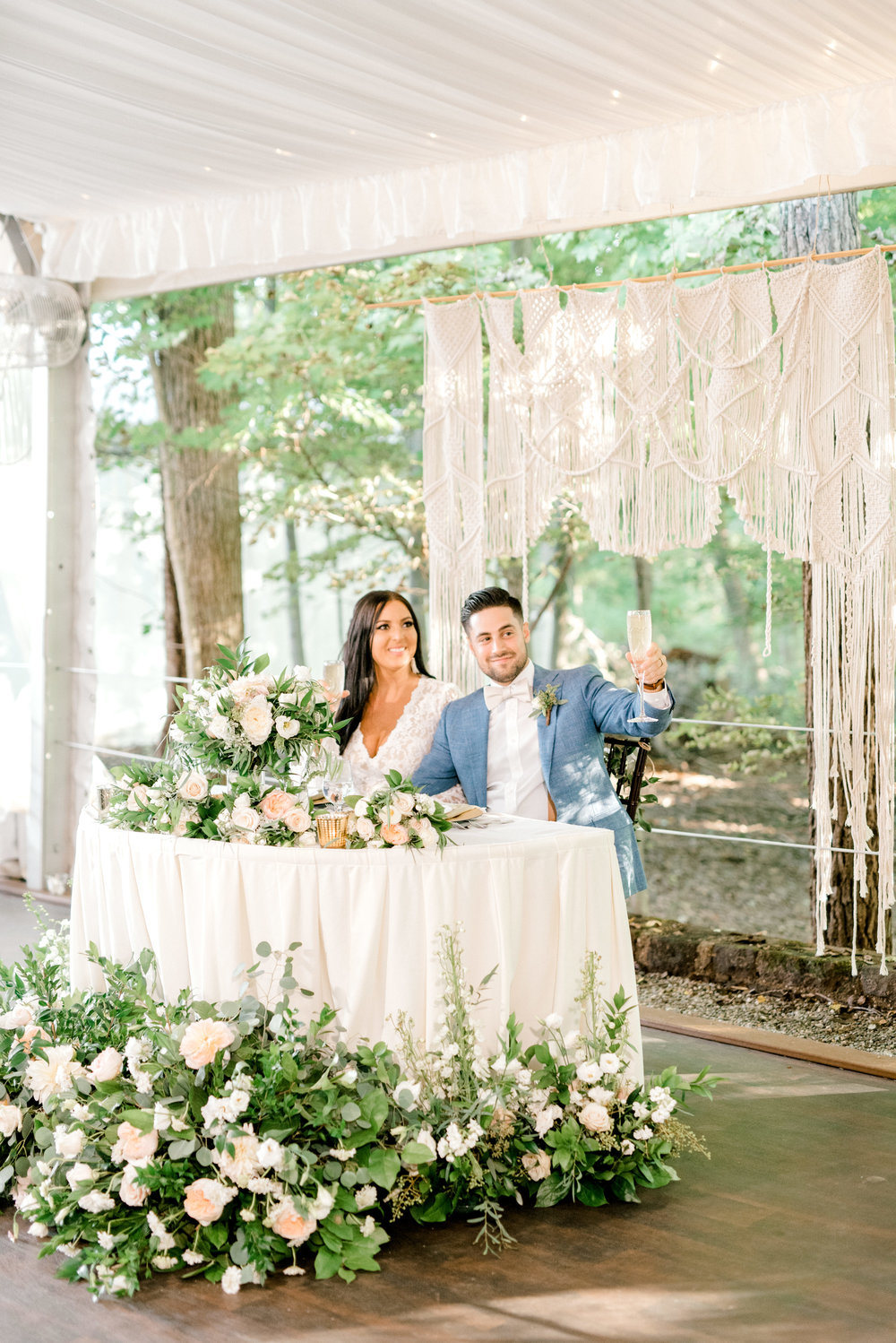 We loved this wild sweetheart table surrounded in whimsical greenery and given a white macrame backdrop from this bright boho chic Tyler Gardens wedding in Bucks County