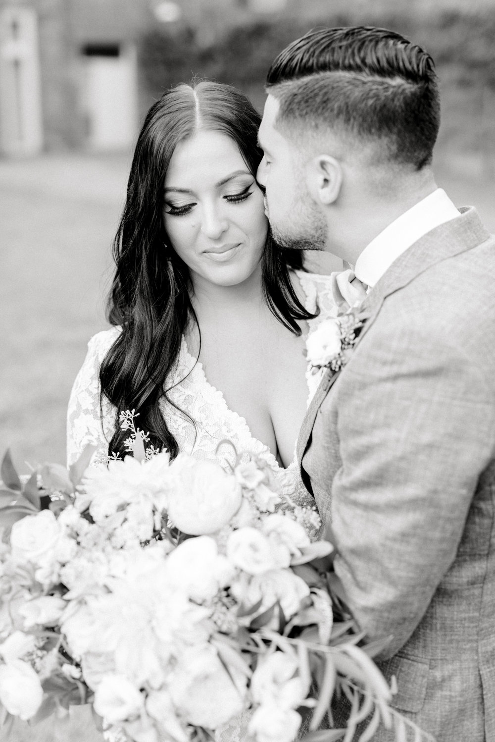 A sweet little moment in black and white with a kiss on the cheek from this bright boho chic Tyler Gardens wedding in Bucks County