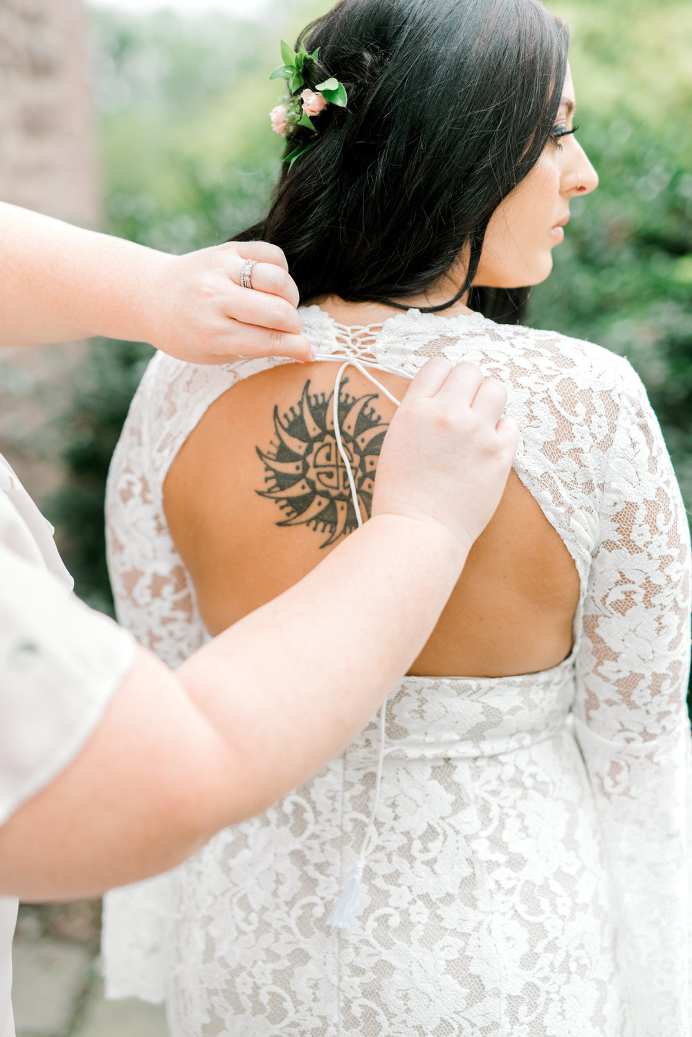 The finishing touches are added to Alicia's dramatic lace BHLDN wedding gown just moments before entering her bright boho chic Tyler Gardens wedding in Bucks County