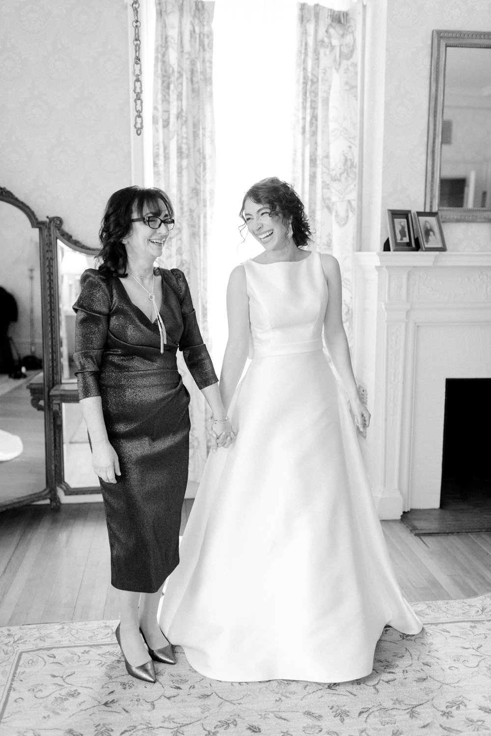 Our lovely bride shares a laugh with her mother, just moments before her romantic and classic wedding day for their french inspired green and white Cairnwood Estate wedding