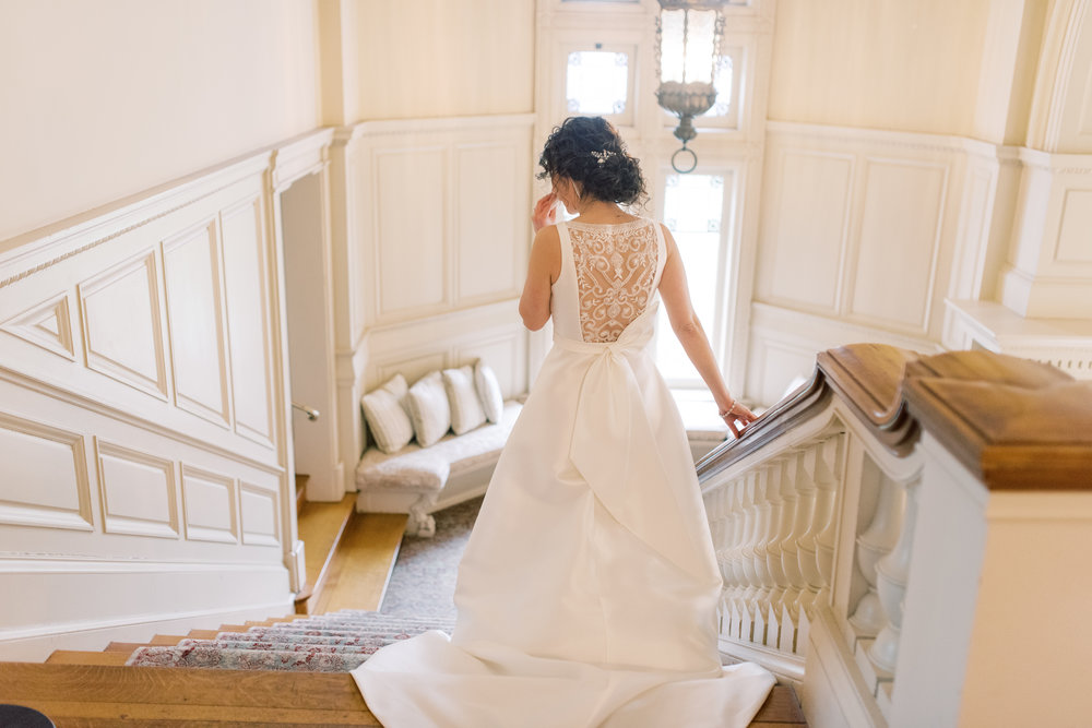 Angjela heads down the staircase for her first look for her romantic and classic wedding day for their french inspired green and white Cairnwood Estate wedding