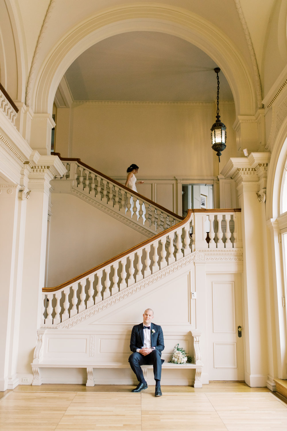 Our bride goes down the grand staircase as our groom waits to see her for the first time at their romantic and classic wedding day for their french inspired green and white Cairnwood Estate wedding