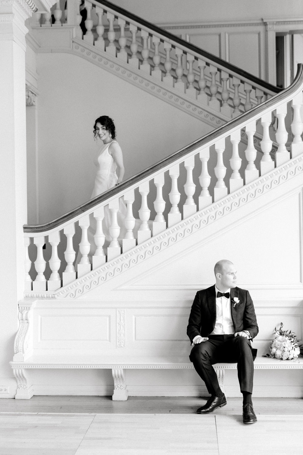 Our bride walks down the grand staircase as her groom waits to see her for the first time for their first look at their romantic and classic wedding day for their french inspired green and white Cairnwood Estate wedding