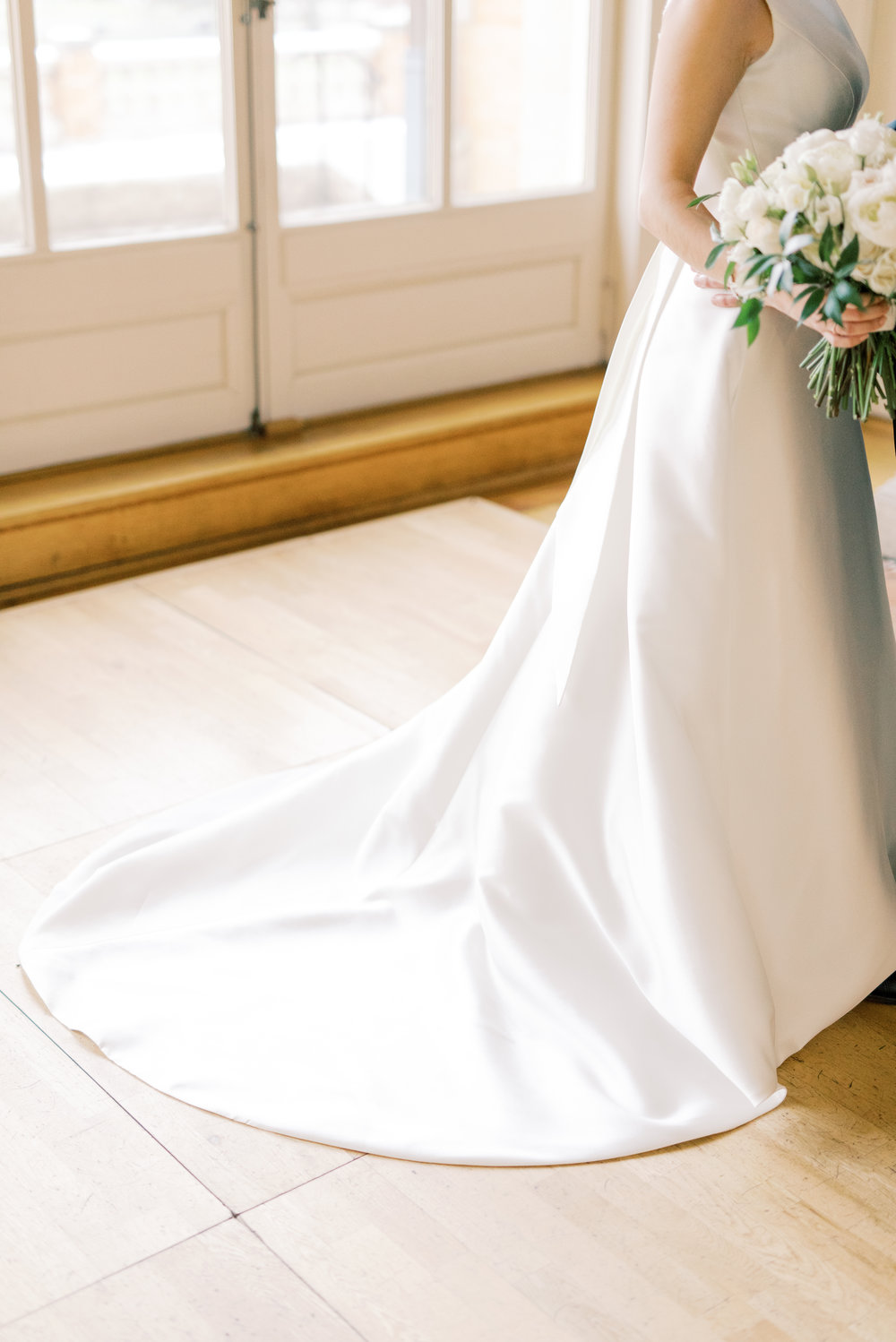 The mini train on this modern structured a-line dress was the perfect touch to let you know that it's a wedding gown from this romantic and classic wedding day for their french inspired green and white Cairnwood Estate wedding