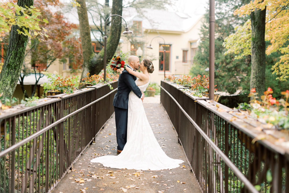 Couple kissing on bridge at romantic modern autumn wedding at Pomme in Radnor. Pomme wedding photographer.