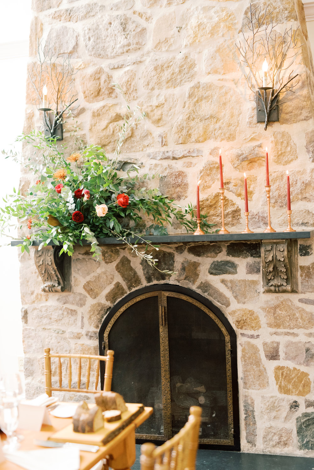 Red floral adorned fireplace at modern autumn wedding at Pomme, Radnor PA. Pomme wedding photographer.