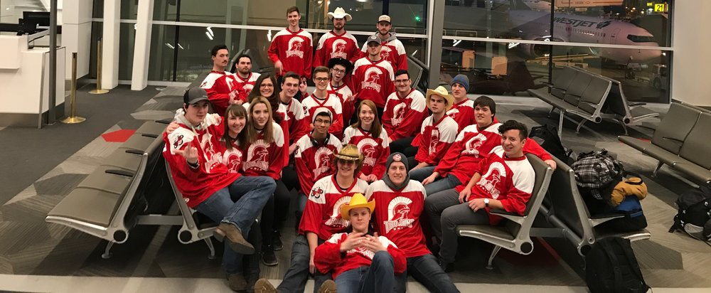 The SAIT team before boarding at YYC — jerseys with thanks to SAIT's Trojans Athletics.