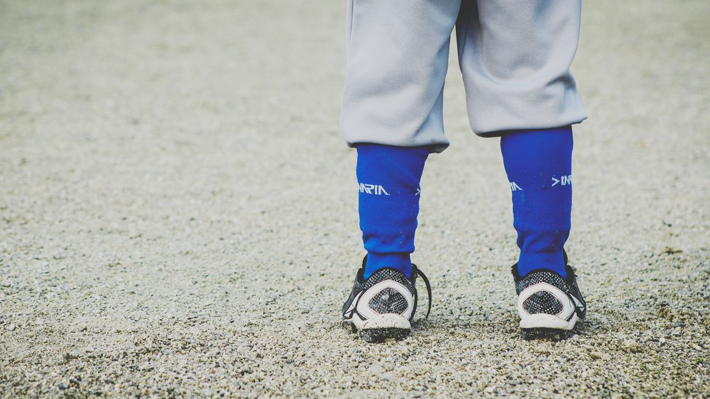 Young baseball player in his cleats and uniform. The sideline parent.