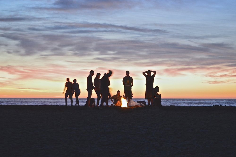 A group of friends having a fire on the beach during sunset.