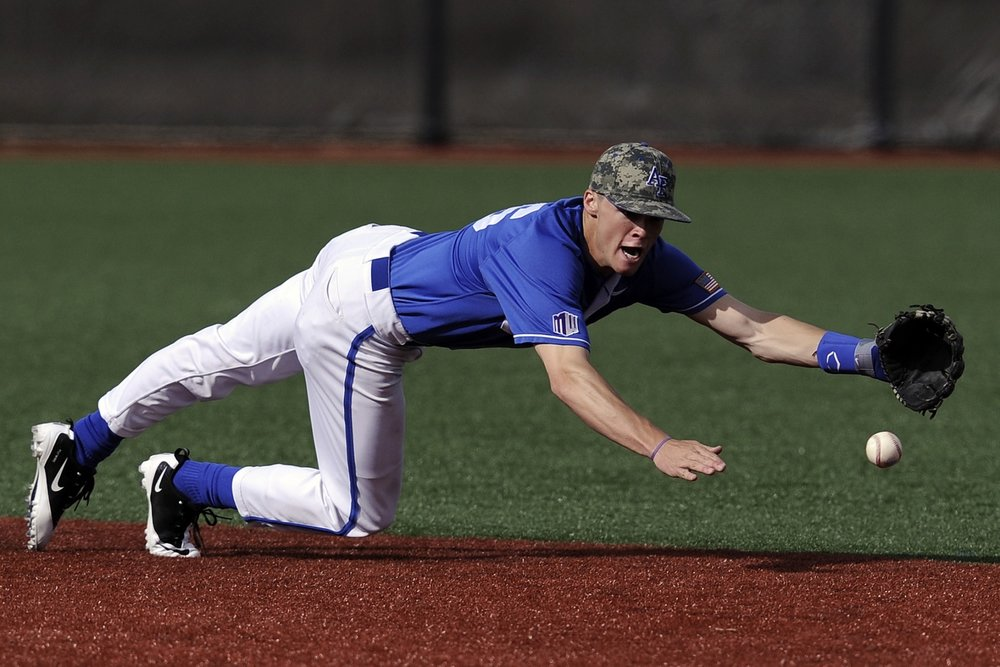 Baseball player diving for a groundball in the infield. The athlete.