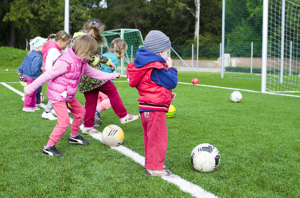 Young kids kicking a soccer ball into the goal. The sideline parent.