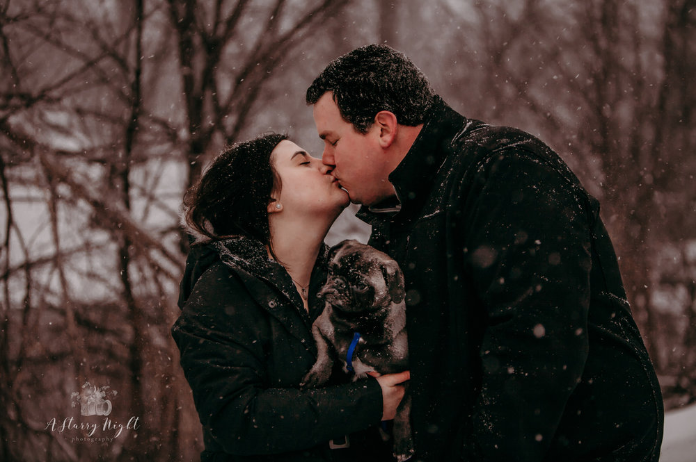 Couple sharing a kiss during their engagement session at the Mountain Town Station in Mount Pleasant,MI