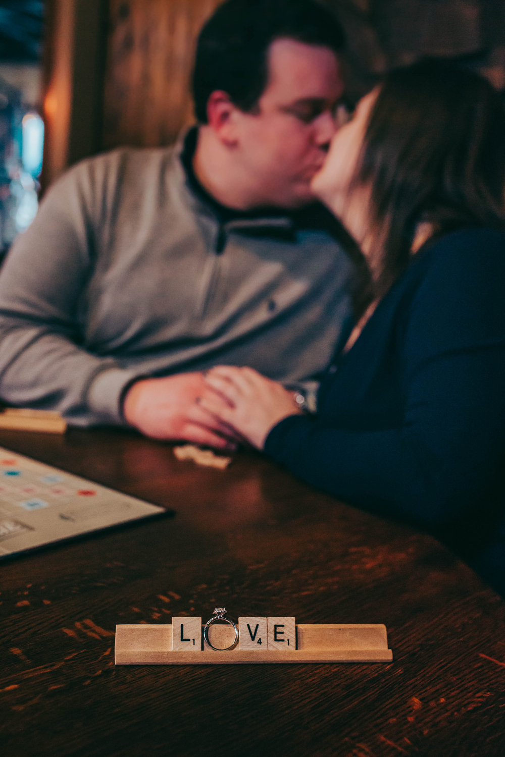 Love with Ring on a Scrabble Board for a Lifestyle Engagement Session with the couple in the background.