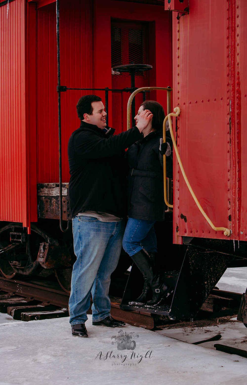 Fiance wiping hair from Brides face during their Engagement Session at the Clare, MI Train Depot