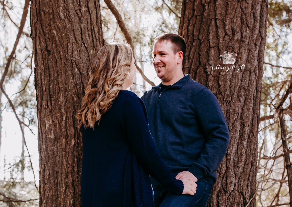 Couple standing by the trees at Crooked River Weddings during their Engagement Session in Gladwin , MI.