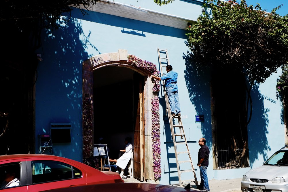 A Business owner decorates his doorway with marigolds.