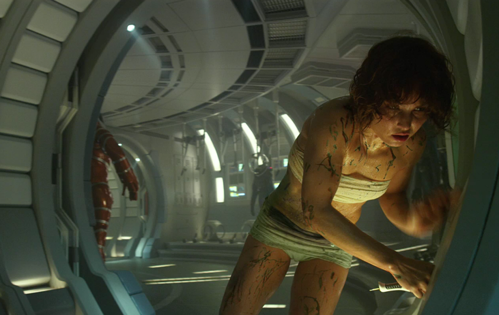 Elizabeth Shaw (Noomi Rapace) flees from the alien fetus she surgically removed from her abdomen.