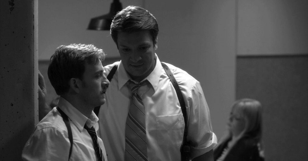 Verges (Tom Lenk) and Dogberry (Nathan Fillion) discuss the villainous cads they apprehended.