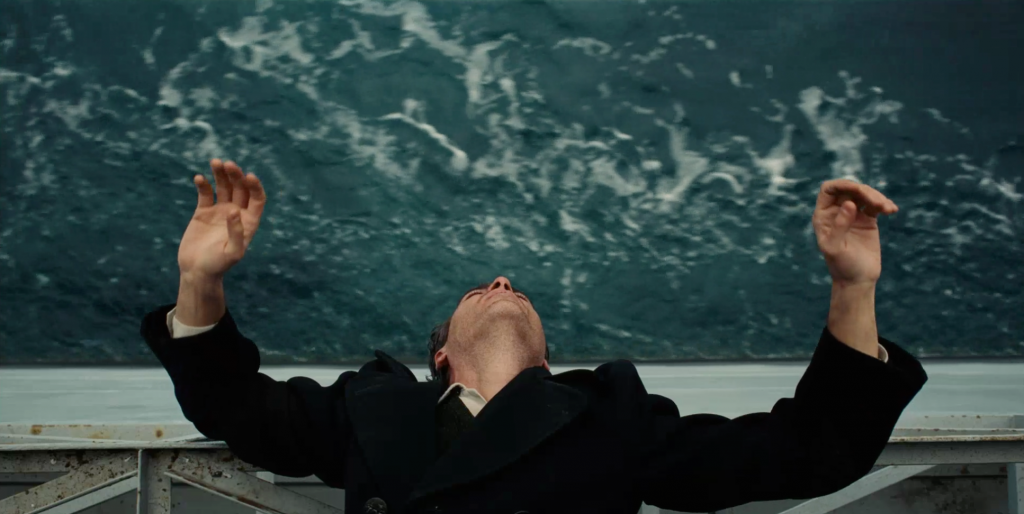 Freddie Quell (Joaquin Phoenix) drifts aimlessly over the Pacific Ocean.