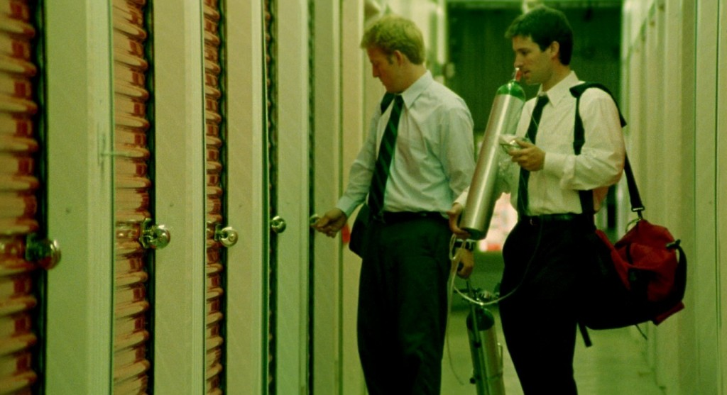 Abe (David Sullivan) and Aaron (Shane Carruth) go to use the machine in its storage facility.