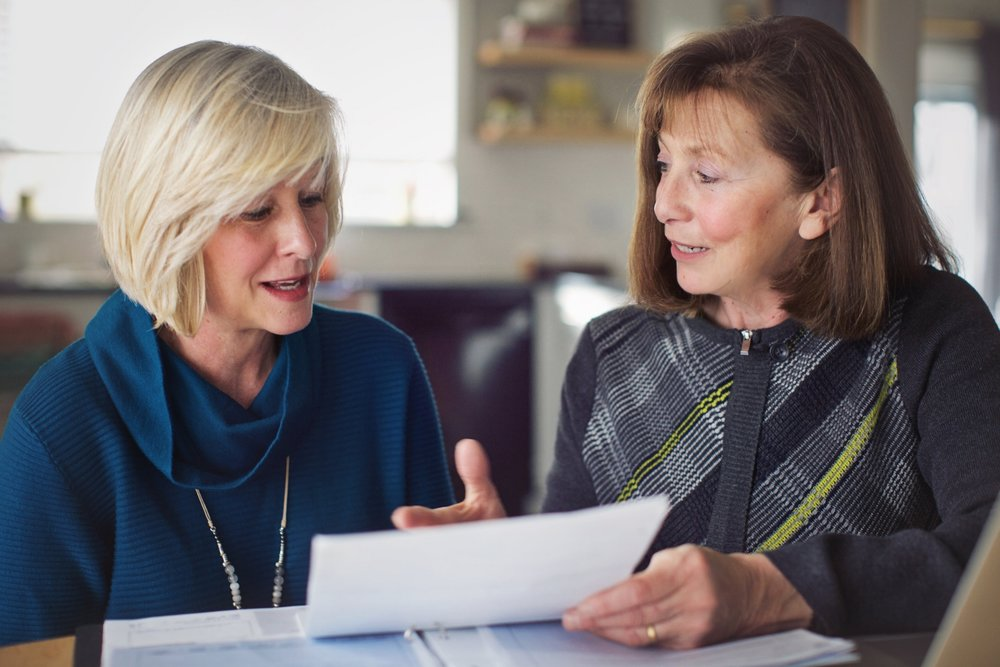 Judy (right) reviews medical insurance records together with one of her clients.