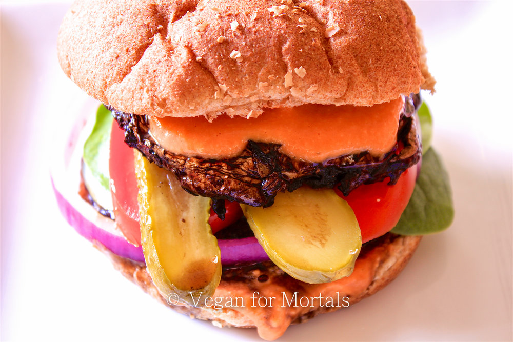 Portobello Mushroom Burger with Red Pepper Hummus Sauce - Looking for another alternative to a typical veggie burger? Try out my portobello mushroom burger! A quick balsamic marinade with garlic and black pepper and you'll be grilling in no time. Top with a zesty red pepper hummus sauce for a tangy zip!