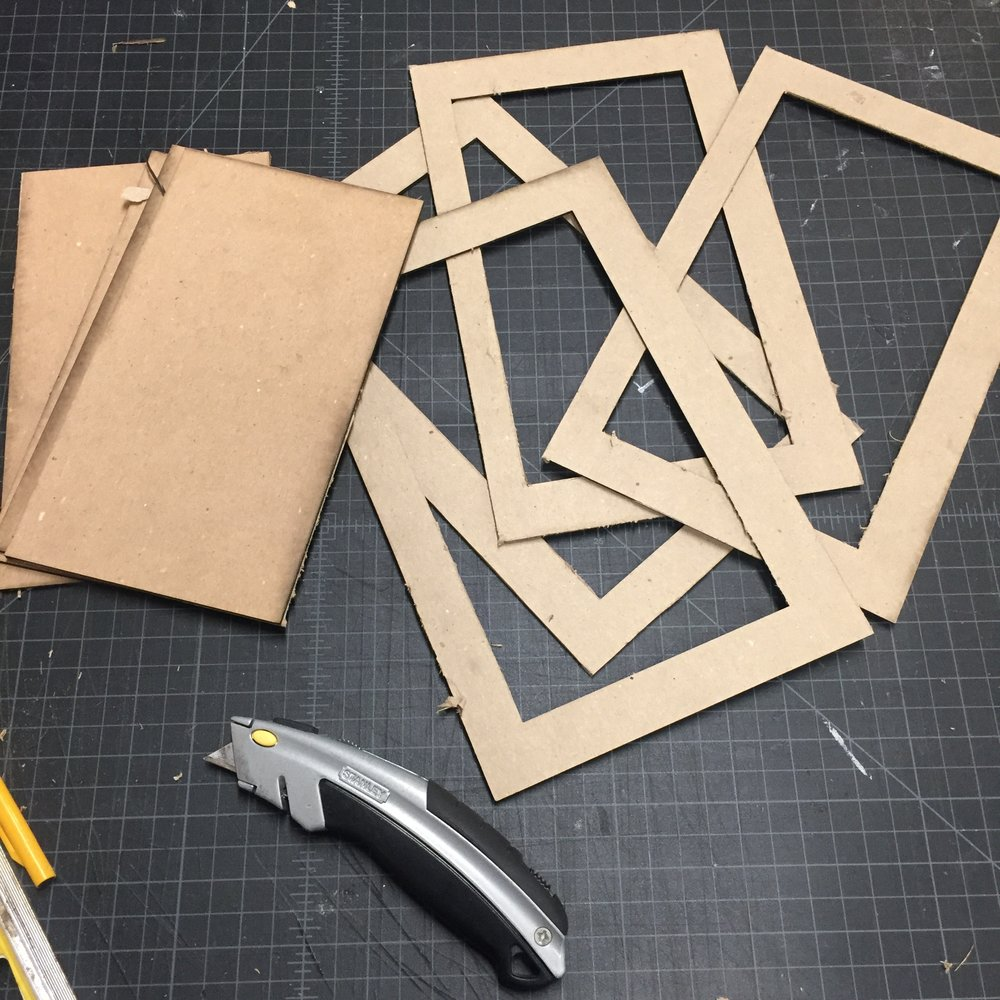 "Laser cut chip board pieces. The ""Frame"" shape was key."
