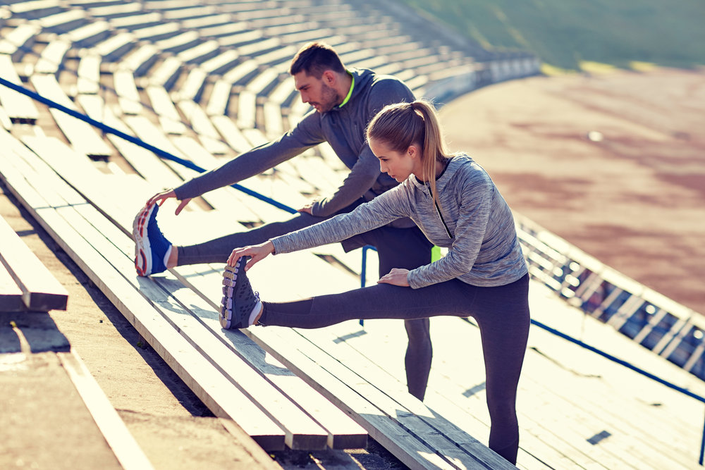 couple-stretching-leg-on-stands-of-stadium-PJHZE23.jpg