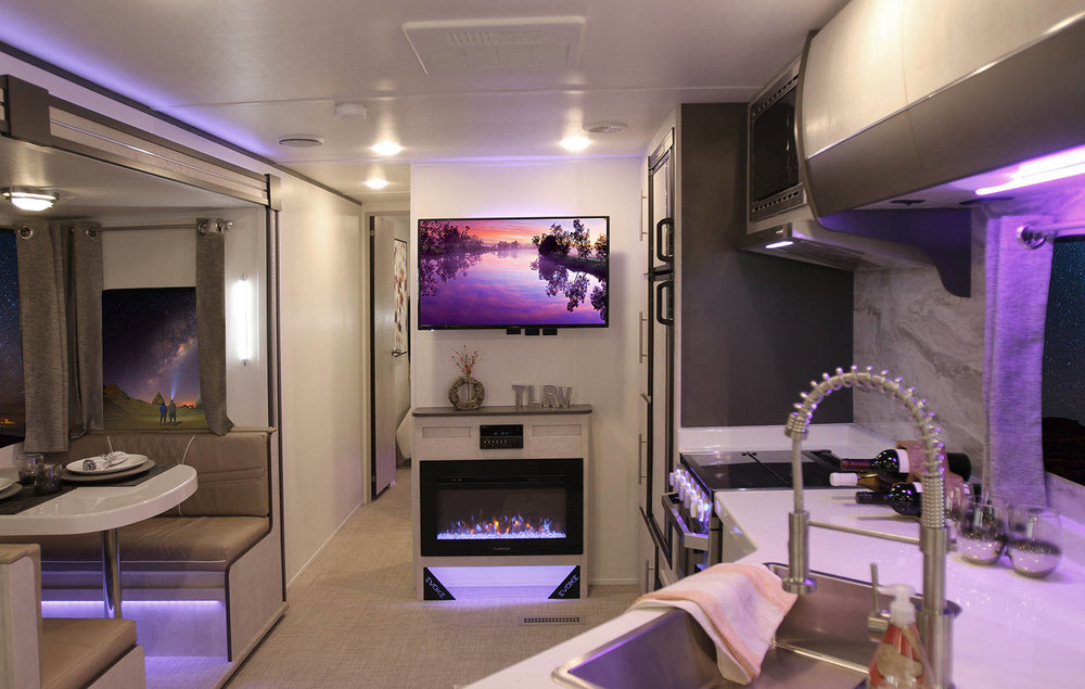 Ambient lighting, contrasting textures, and a fireplace give the EVOKE series the feel of a cozy loft. Credit: Travel Lite RV