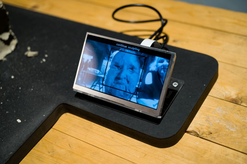 Dries Depoorter - Face Detected (2018) - 'Face Detected' is an installation where several artists are invited to modelling clay portraits, while a computer programme is following their accomplishments through a camera. As soon as the software detects a human face, the artist is notified that the work is finished.