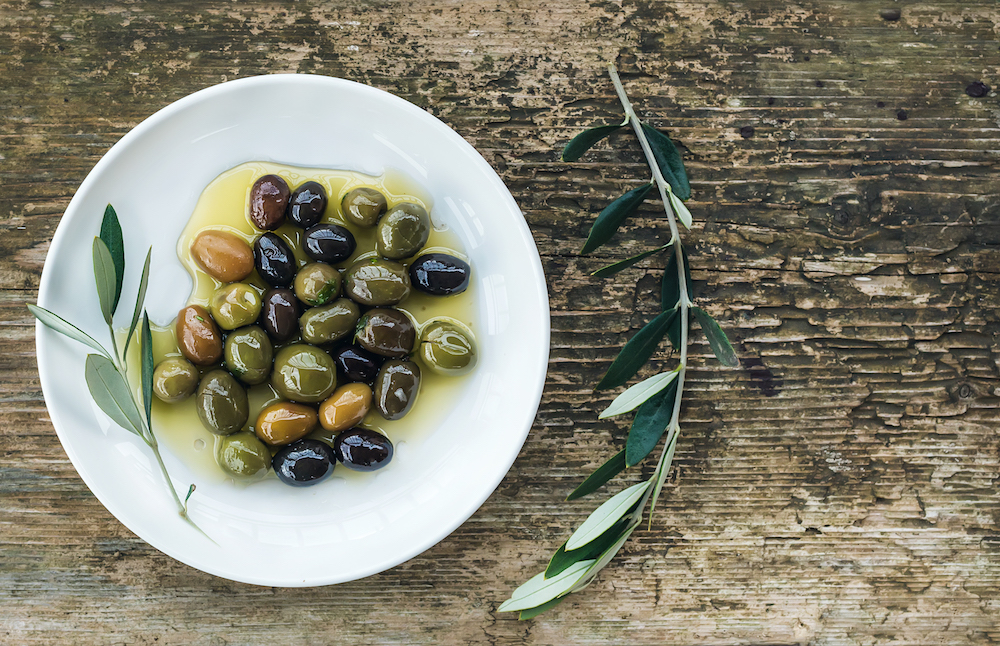 plate-of-mediterranean-olives-in-oil-with-tree-PD3FXRN.jpg