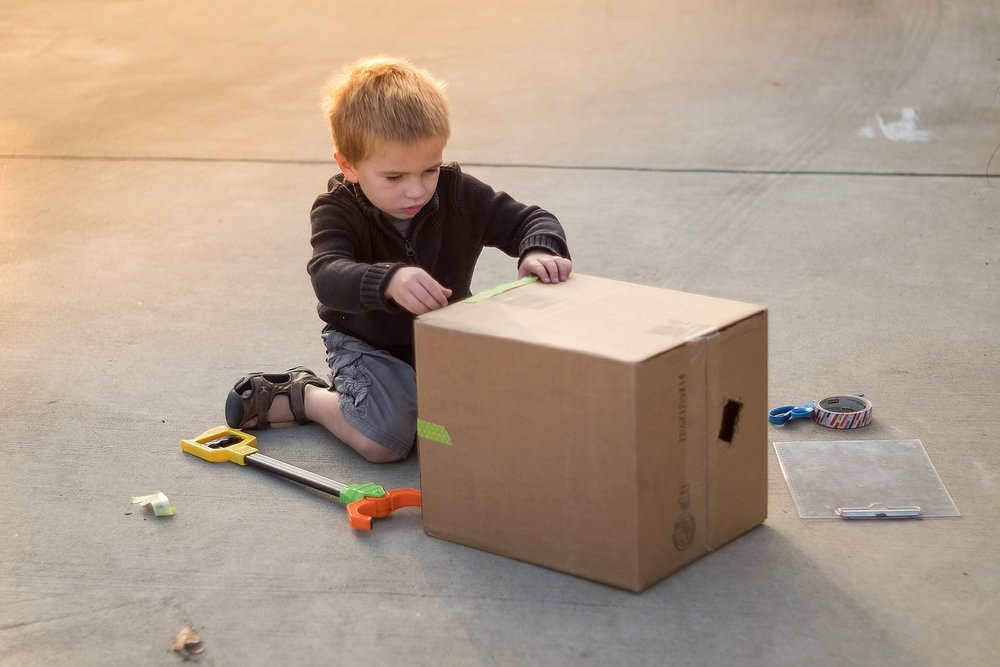 Erica Faith Walker takes a golden hour photo of a boy playing with a box in Claremont, CA.