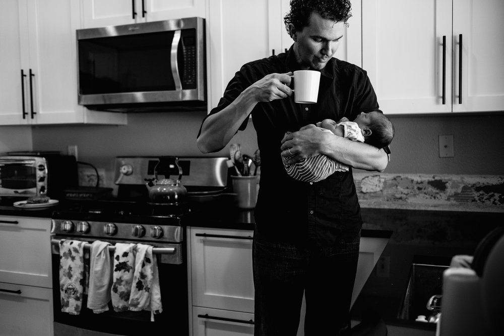 A dad holds his newborn daughter during an in-home session in Rancho Cucamonga by Erica Faith Photography.