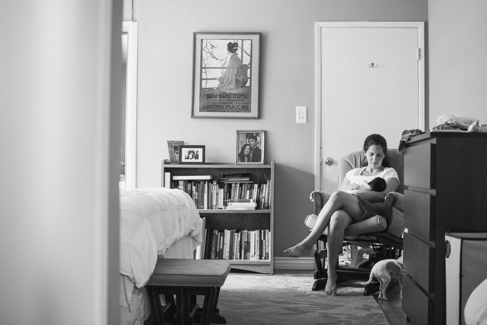 A photo of a nursing mom relaxes with her baby at her in-home newborn session in Claremont taken by Erica Faith Photography.