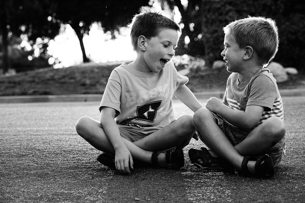 There are no distractions from his blue shirt or the green grass across the street. This is a black and white photo about the bond between brothers.
