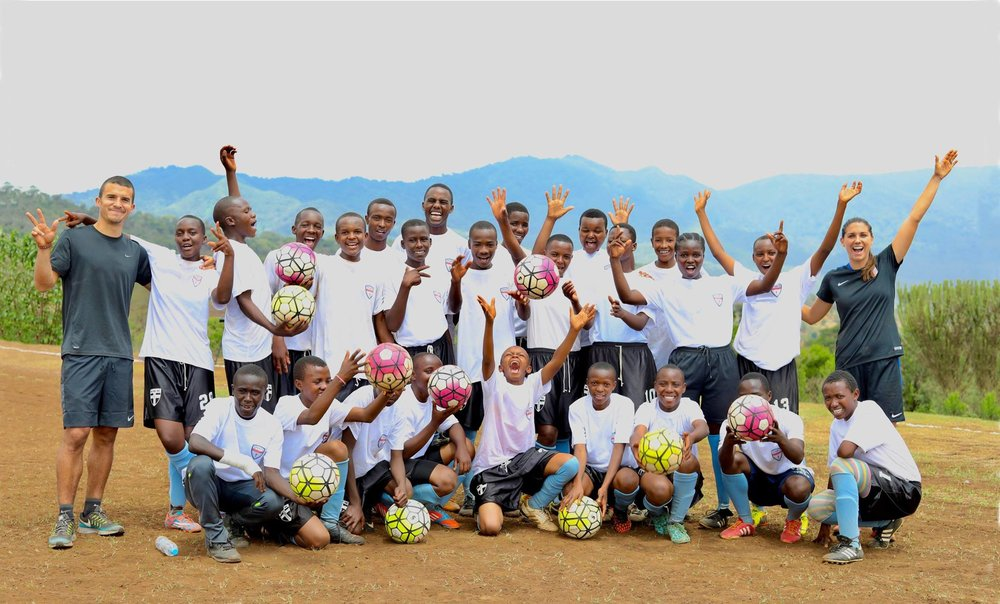Sports Envoys and U.S. Women's National Team member, Alex Morgan, and Orlando City player Servando Carrasco celebrate with youth after a clinic in Tanzania.  2017.