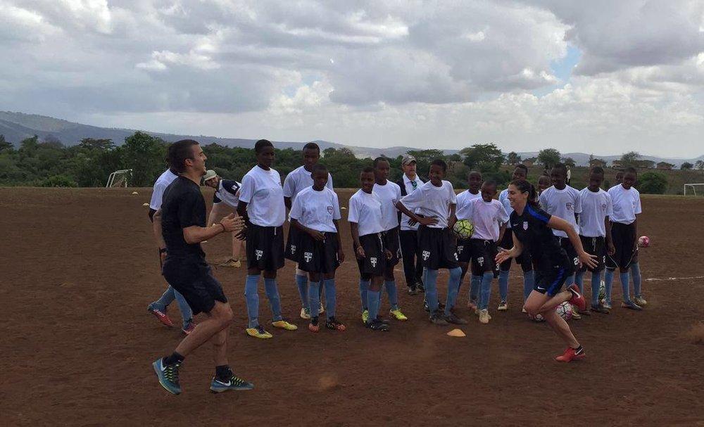 Sports Envoys and U.S. Women's National Team member, Alex Morgan, and Orlando City player Servando Carrasco demonstrate footwork in Tanzania. 2017.