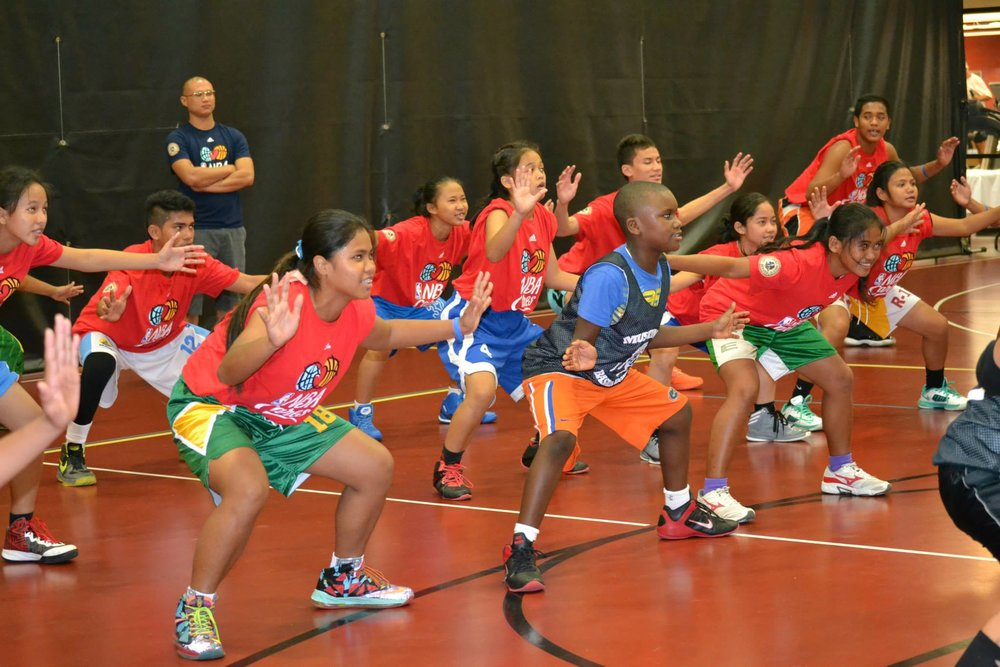 Sports Visitors from the Philippines work on their defensive positioning with coaches from NBA Cares. 2014.