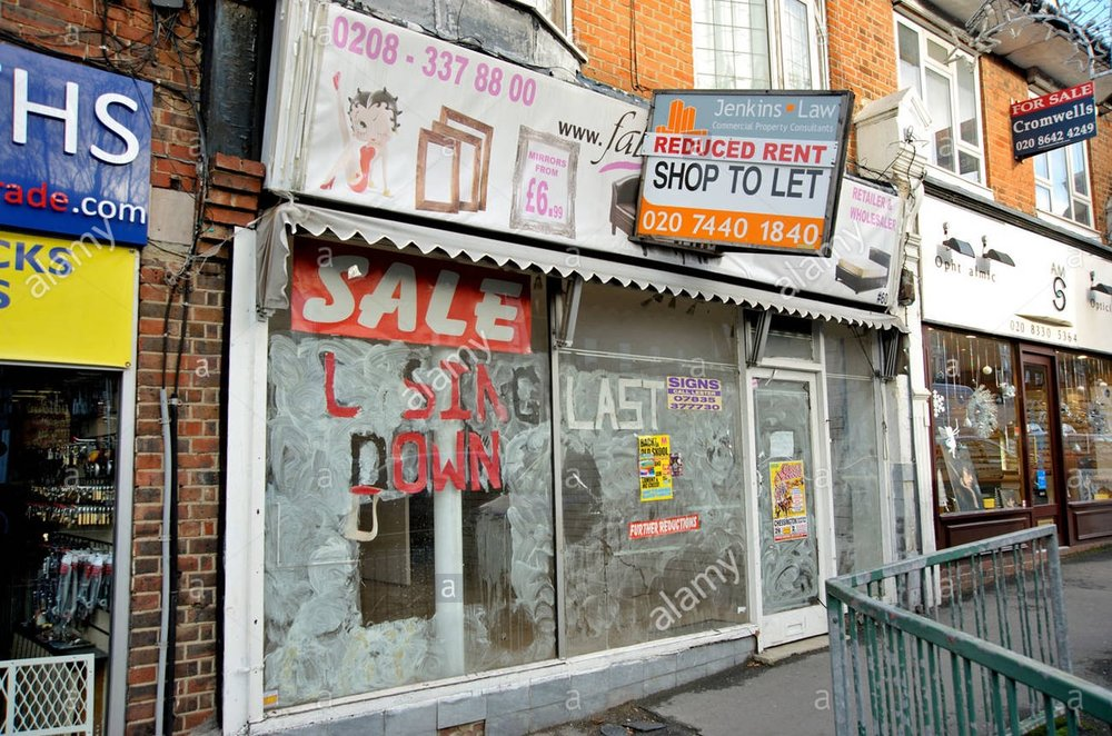 an-empty-shop-in-a-suburban-london-high-street-with-closing-down-sale-CB8W4R.jpg